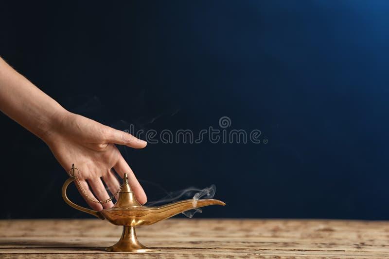 Frau, die magische Wunderlampe auf Tabelle reibt lizenzfreie stockfotografie