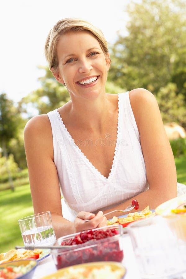 Frau, die Mahlzeit im Garten genießt lizenzfreie stockfotografie
