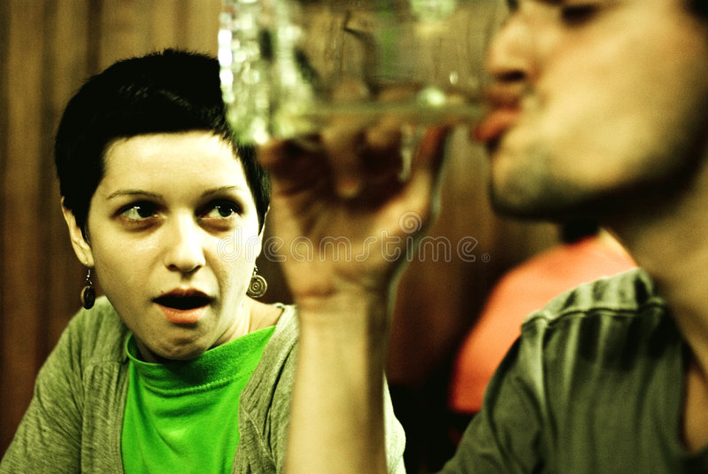 Frau, die am Manntrinken gafft lizenzfreies stockbild