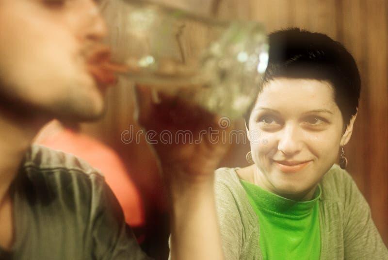 Frau, die am Manntrinken lächelt lizenzfreies stockfoto