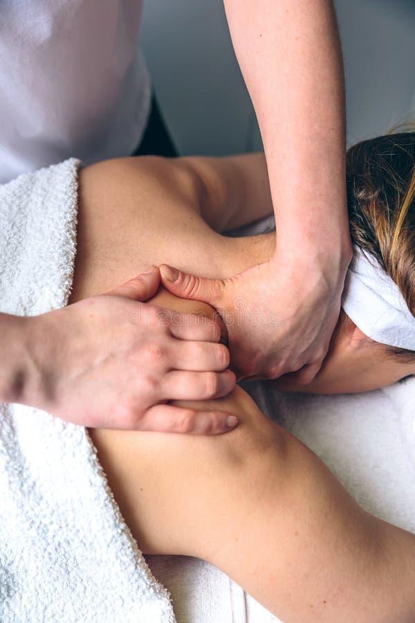 Frau, die Massage auf Schultern in der klinischen Mitte empfängt lizenzfreie stockbilder