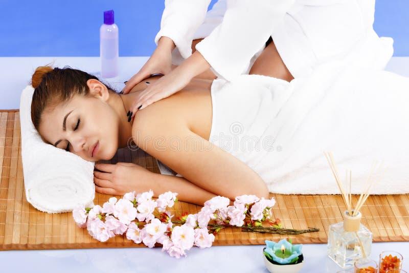 Frau, die Massage der Karosserie im Badekurortsalon hat Aufbau mit Badeöl und Seifen stockbilder