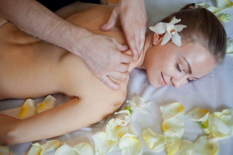 Frau, die Massage im Badekurortsalon hat Frauenfuß im Wasser Mit den rosafarbenen Blumenblättern stockfotografie