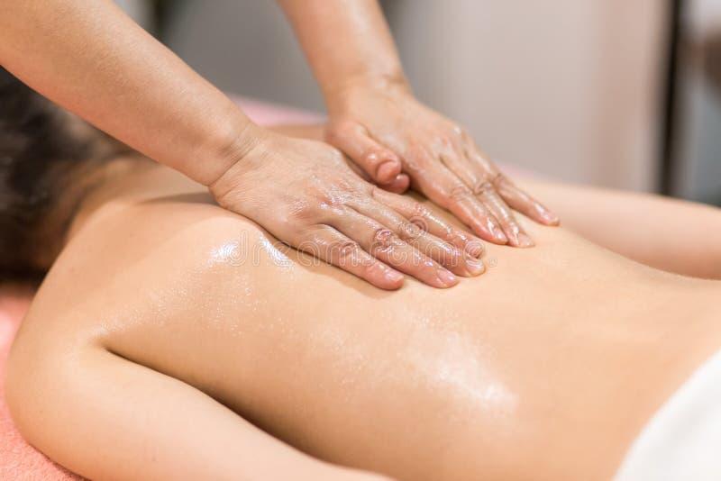 Frau, die Massage mit Massage-Öl in einem Badekurort hat lizenzfreie stockfotos