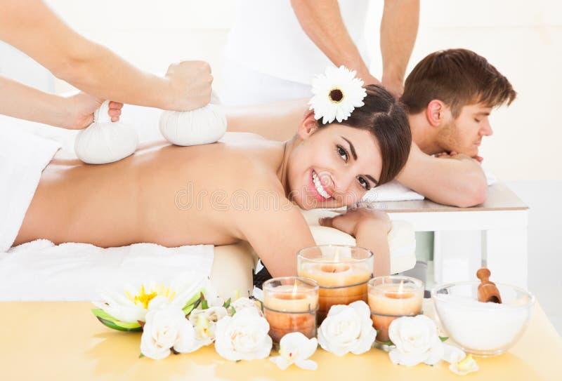 Frau, die Massage mit Kräuterkompressenstempeln empfängt stockfotografie
