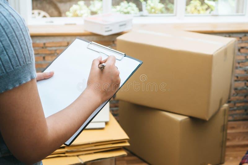 Frau, die Material in der Pappschachtel überprüft lizenzfreies stockbild