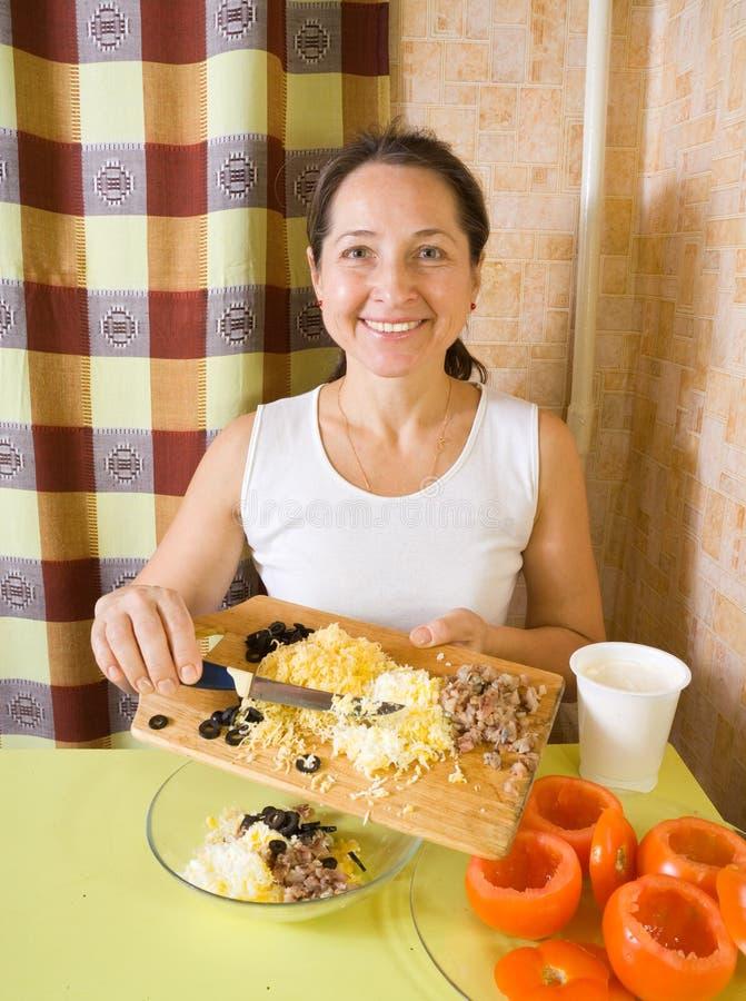Frau, die Material für Salat der angefüllten Tomate bildet lizenzfreie stockbilder