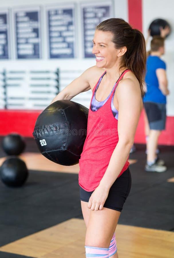 Frau, die Medizinball im Fitness-Club hält lizenzfreies stockbild