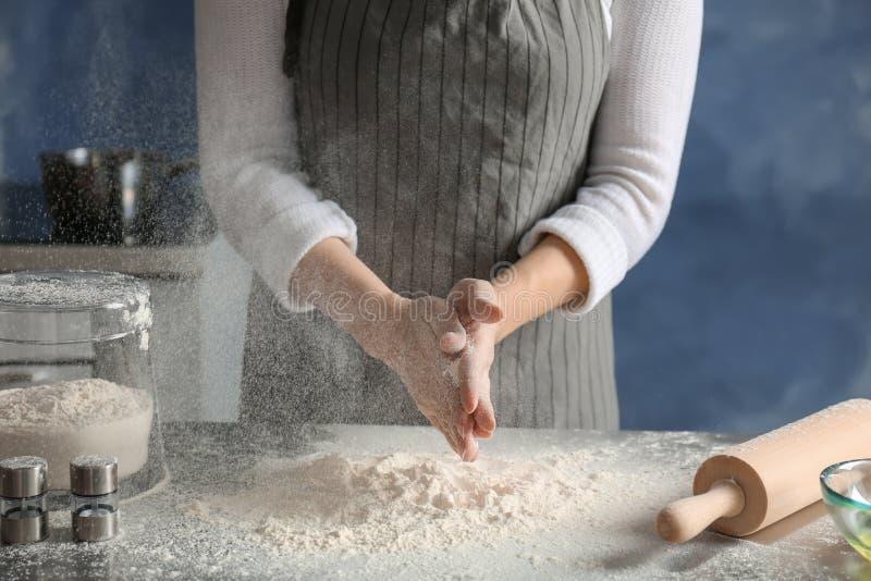 Frau, die Mehl über Tabelle besprüht lizenzfreie stockfotografie