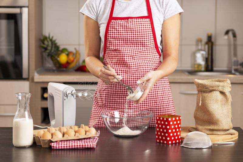 Frau, die Mehl in eine Mischschüssel hinzufügt stockfotografie