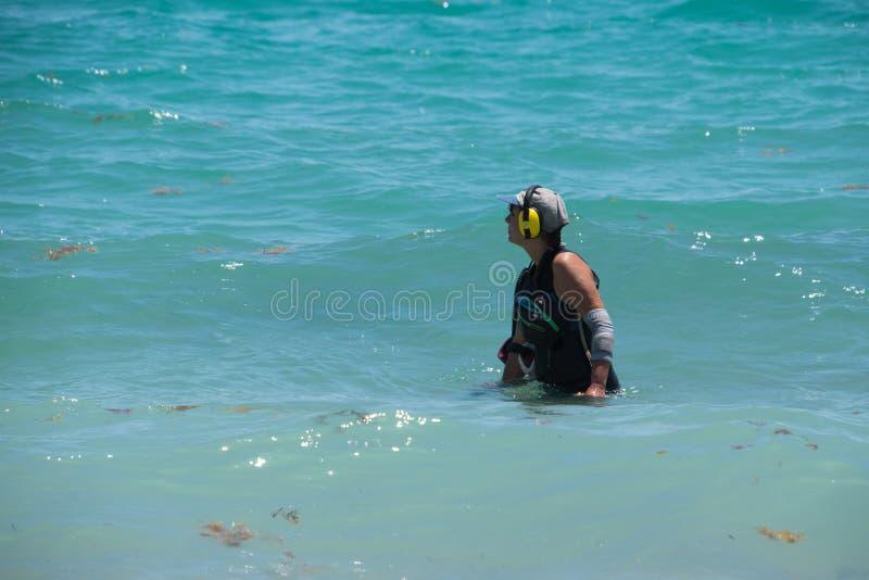 Frau, die Metalldetektor im Ozean verwendet lizenzfreie stockfotos