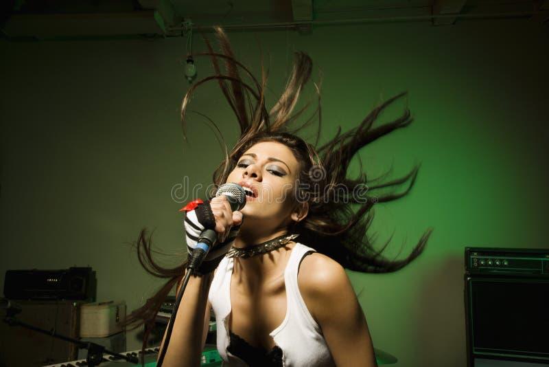 Frau, die in mic singt. stockbilder