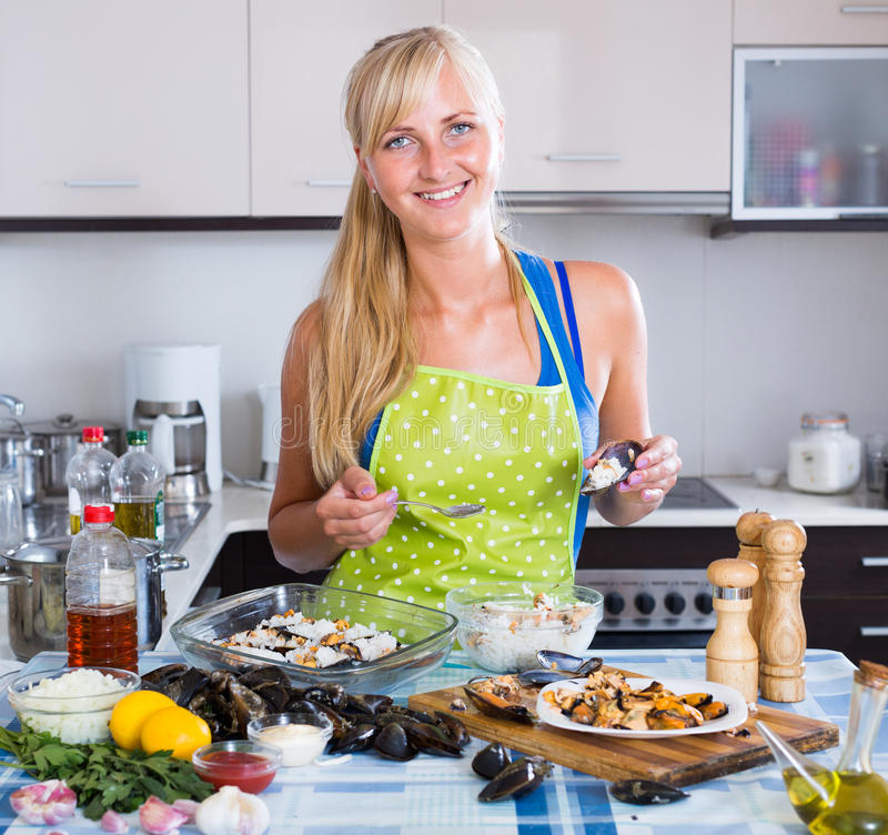 Frau, die Miesmuscheln mit Reis zubereitet lizenzfreie stockbilder