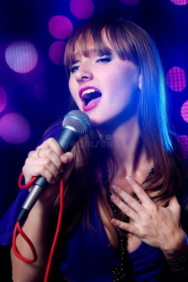 Frau, die in Mikrofon singt stockbild