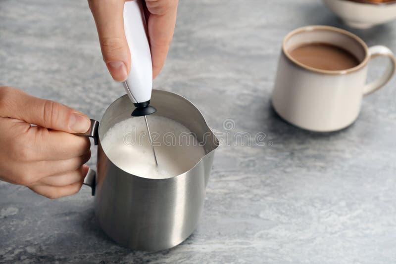Frau, die Milch frother im Werfer nahe Tasse Kaffee verwendet stockfotos
