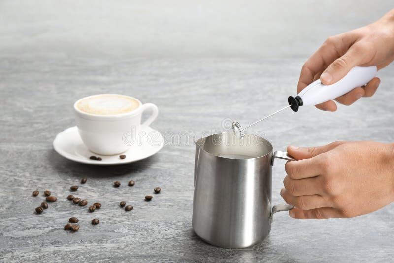 Frau, die Milch frother im Werfer nahe Tasse Kaffee verwendet stockbilder