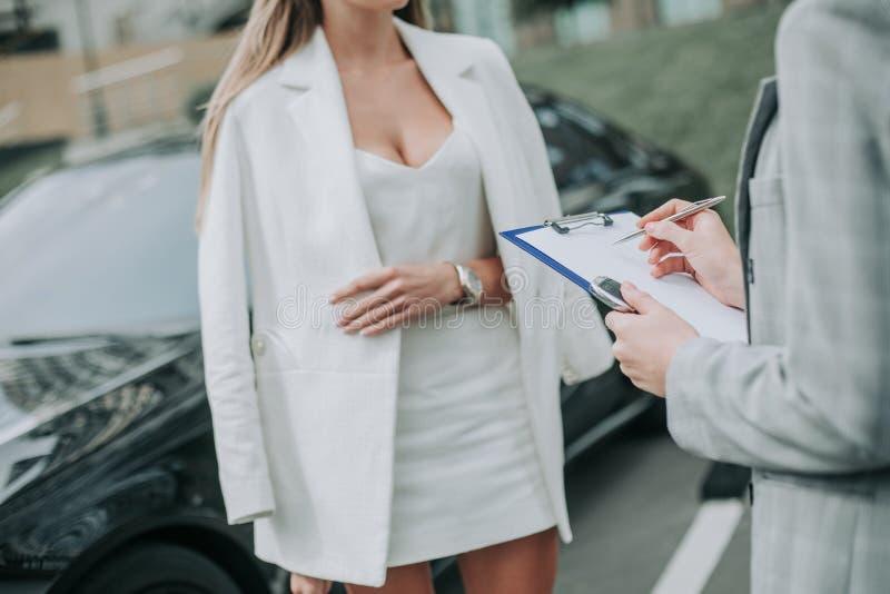 Frau, die mit Arbeitskraft nahe Auto draußen nimmt stockbilder