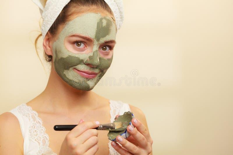 Frau, die mit Bürstenlehm-Schlammmaske auf ihr Gesicht zutrifft stockfoto