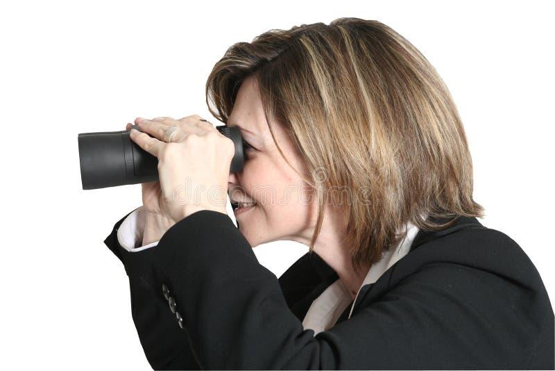 Frau, die mit Binokeln schaut stockbild