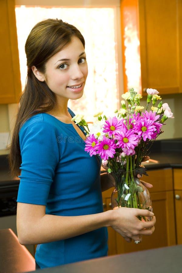 Frau, die mit Blumen aufwirft stockbild