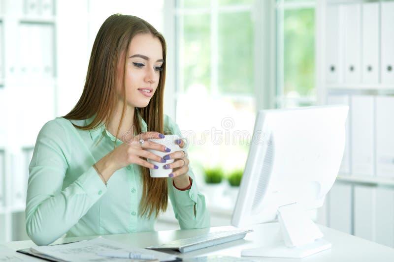 Frau, die mit Computer arbeitet stockfotografie
