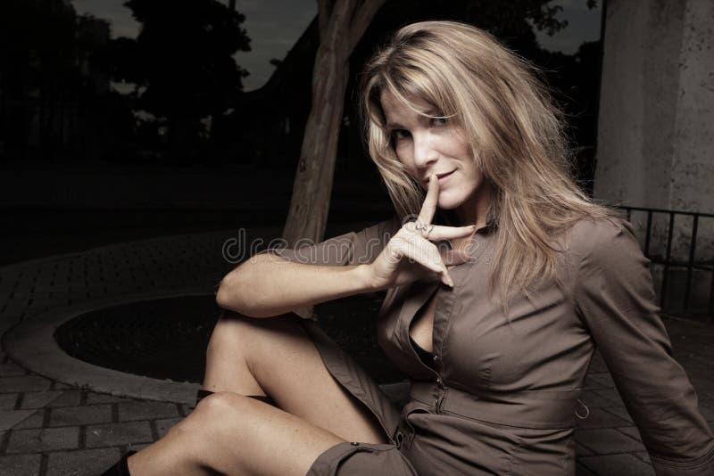 Frau, die mit dem Finger auf Lippen sitzt lizenzfreie stockbilder