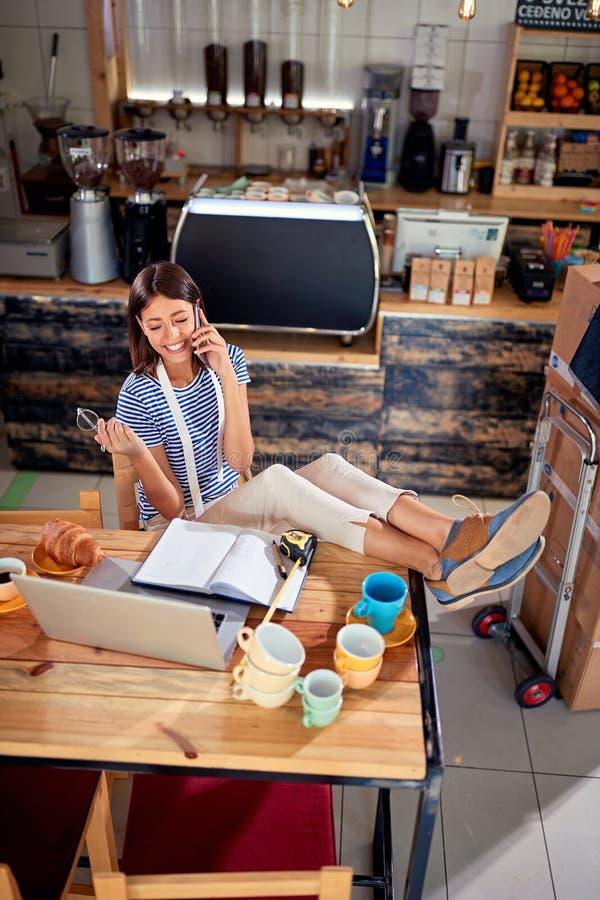 Frau, die mit dem Laptop bereit, ihr Café zu öffnen arbeitet lizenzfreies stockbild