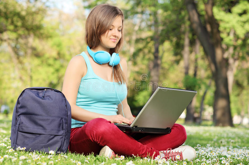 Frau, die mit dem Laptop gesetzt im Park studiert stockfoto