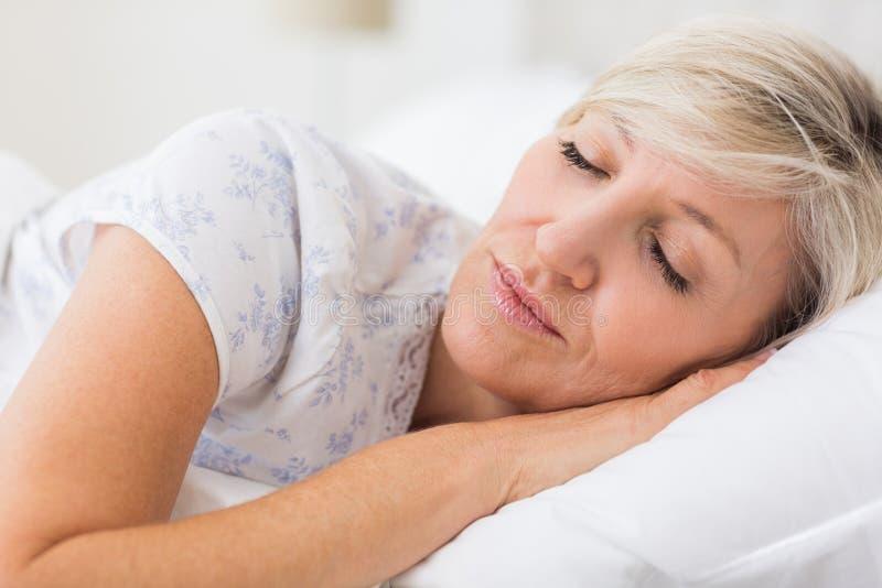 Frau, die mit den Augen geschlossen im Bett schläft stockfotografie