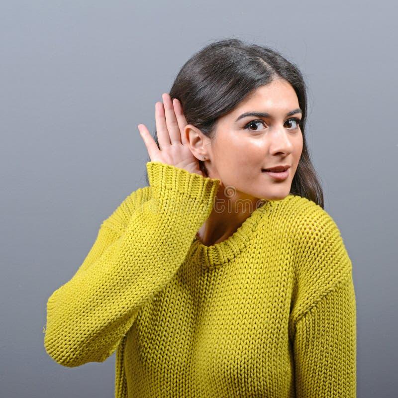 Frau, die mit der Hand auf Ohrkonzept gegen grauen Hintergrund hört stockbilder