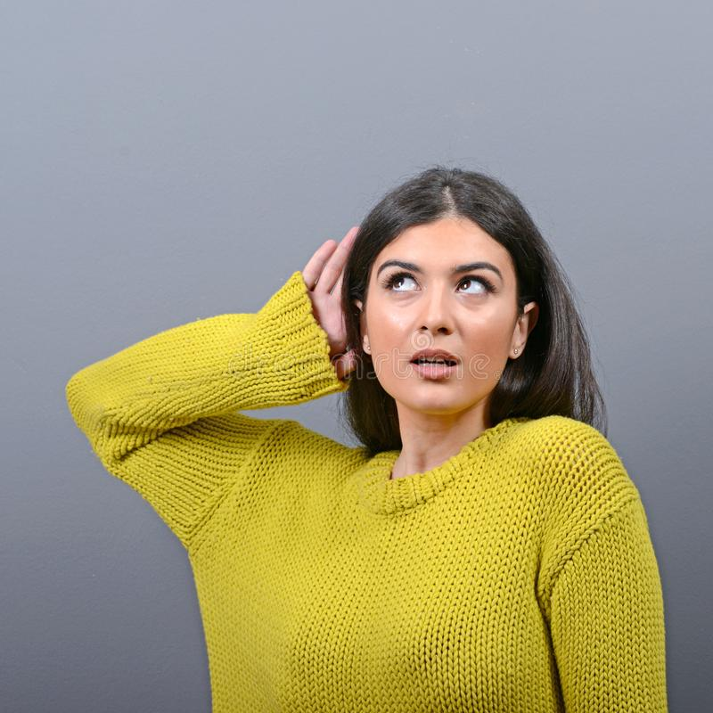 Frau, die mit der Hand auf Ohrkonzept gegen grauen Hintergrund hört stockfoto