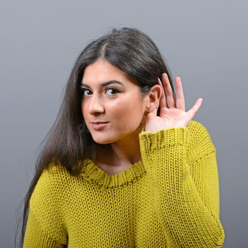 Frau, die mit der Hand auf Ohrkonzept gegen grauen Hintergrund hört stockbild