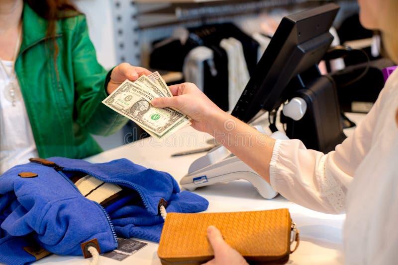Frau, die mit Dollar im Kleidungsshop zahlt stockfotografie