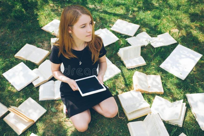 Frau, die mit ebook Leser und Buch lernt Wahl zwischen moderner pädagogischer Technologie und traditioneller Weisenmethode Mädche lizenzfreie stockfotografie
