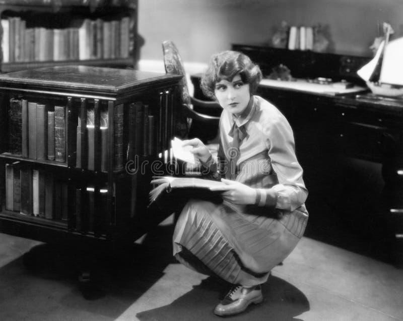 Frau, die mit einem Buch in ihrer Bibliothek findet einen Buchstaben knit (alle dargestellten Personen sind nicht längeres lebend stockfoto