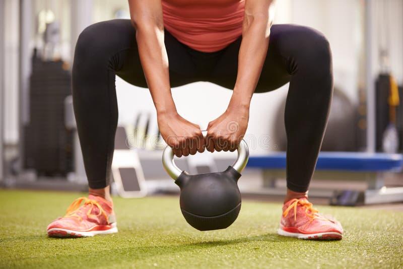 Frau, die mit einem kettlebell Gewicht, Vorderansichtniedrigabschnitternte trainiert stockfotos