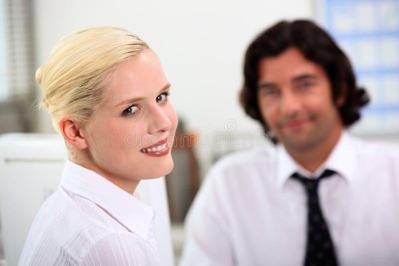 Frau, die mit einem Kollegen sitzt lizenzfreies stockbild