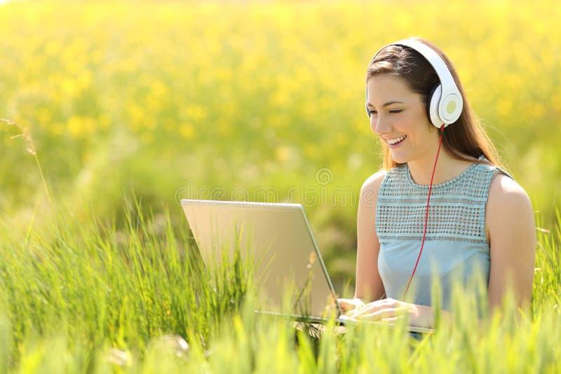 Frau, die mit einem Laptop auf einem Gebiet im Sommer arbeitet lizenzfreie stockfotografie