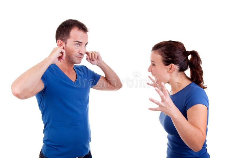 Frau, die mit einem Mann, er mit den Händen auf Ohren schreit stockfoto