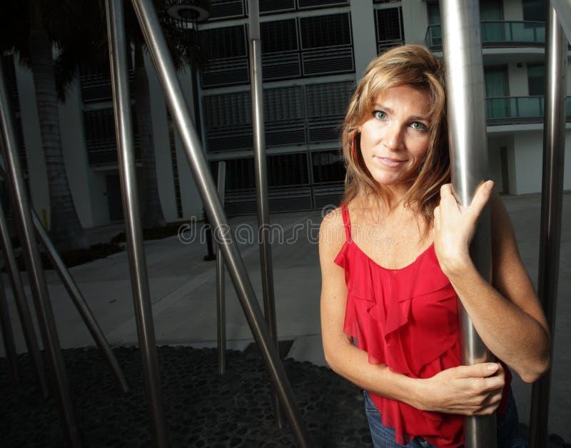 Frau, die mit einem Metallpol aufwirft stockfotografie