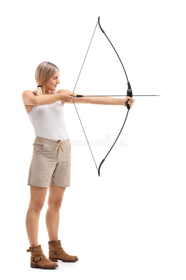 Frau, die mit einem Pfeil und einem Bogen zielt stockfoto