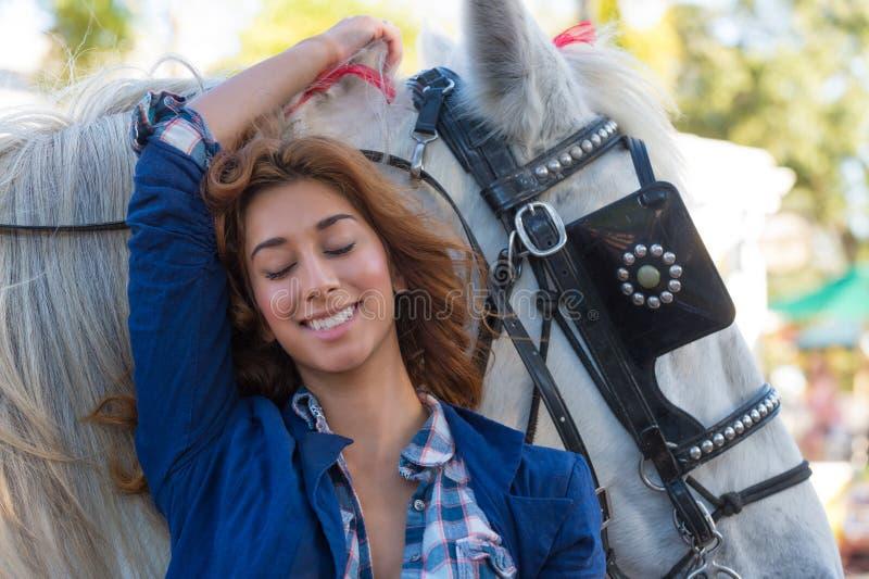 Frau, die mit einem Pferd lächelt lizenzfreie stockfotografie