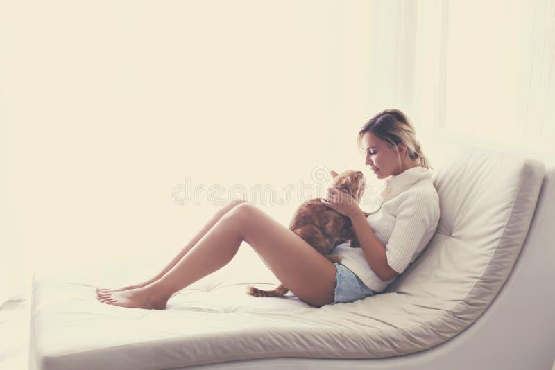 Frau, die mit einer Katze spielt lizenzfreies stockfoto
