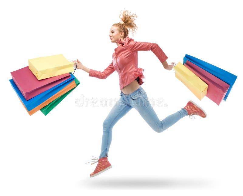 Frau, die mit Einkaufstaschen läuft stockbilder