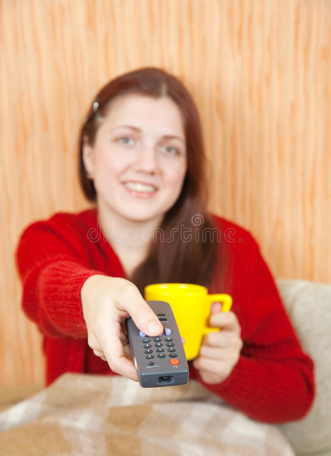 Frau, die mit Fernsehentfernter station lächelt lizenzfreie stockfotografie