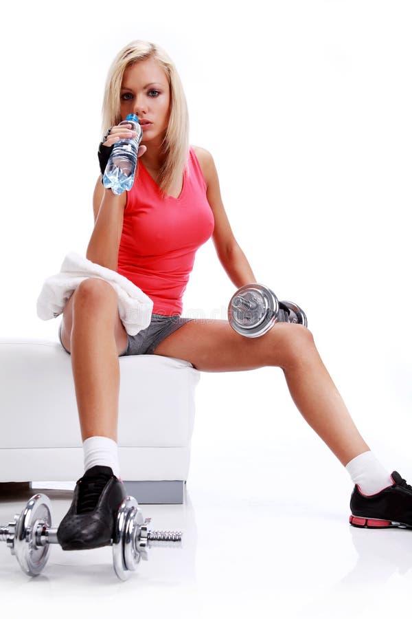 Frau, die mit Flasche Wasser in den Händen sitzt lizenzfreie stockfotos