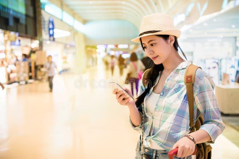 Frau, die mit Gepäck am Flughafen steht stockfotografie