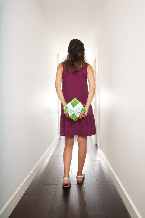 Frau, die mit Geschenk auf ihr zurück geht stockfotografie