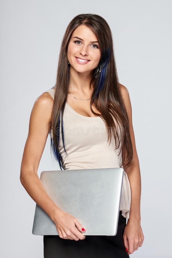 Frau, die mit geschlossenem Laptop steht lizenzfreie stockfotos