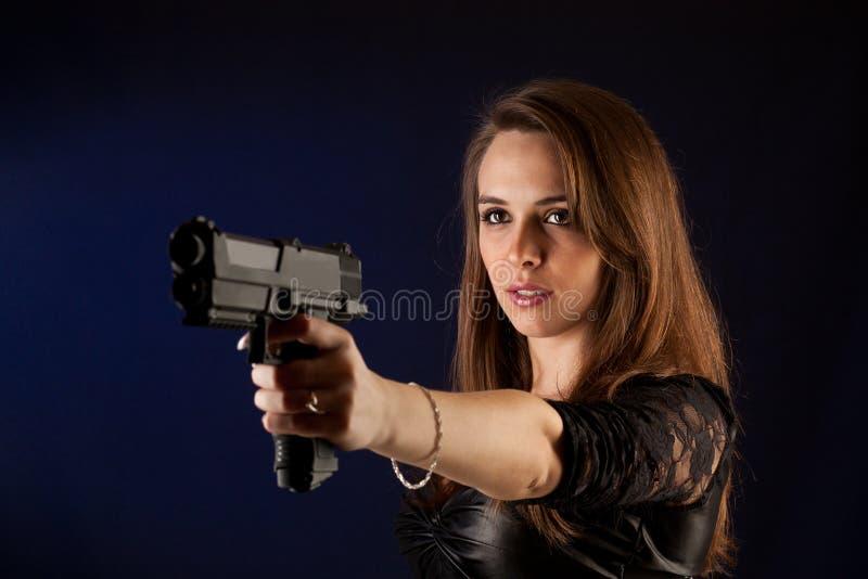 Frau, die mit Gewehren aufwirft lizenzfreie stockfotografie